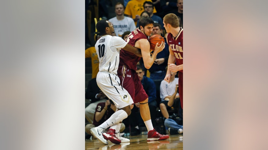 Elon's Tony Sabato, center, fights for control of the ball with Colorado's Tre'Shaun Fletcher, left, during the first half of an NCAA college basketball game in Boulder, Colo., Friday, Dec. 13, 2013. (AP Photo/Brennan Linsley)