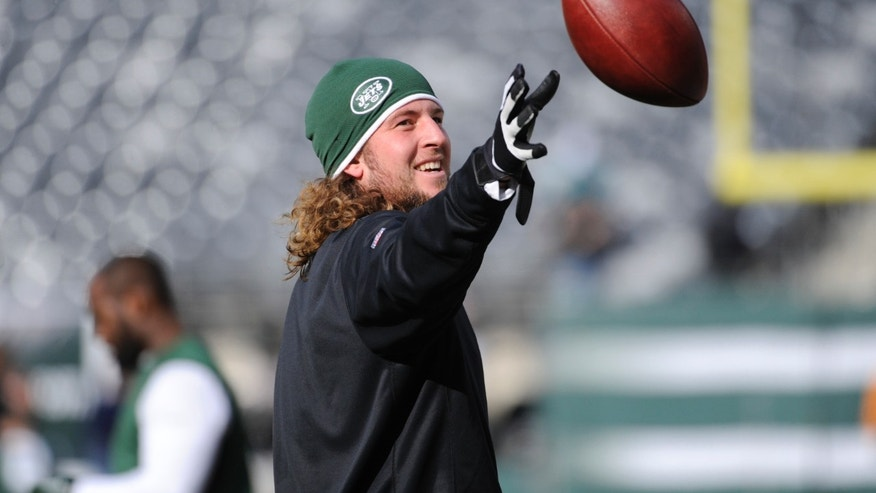 "ADVANCE FOR WEEKEND EDITIONS, DEC. 14-15 - FILE - In this Dec. 1, 2013 file photo, New York Jets tight end Zach Sudfeld works out before an NFL football game against the Miami Dolphins, in East Rutherford, N.J. Sudfeld could have given up on football a few years ago, just as many people told him to. The metal dog tag he wears under his football pads that he got from his grandfather with the Winston Churchill quote engraved on it epitomizes his journey: ""Never, never give up.""  (AP Photo/Bill Kostroun, File)"