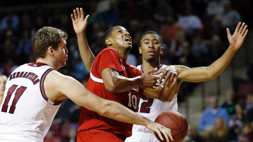 Northern Illinois' Darrell Bowie (10) has the ball striped between Massachusetts' Tyler Bergantino (11) and Trey Davis (12) in the first half of an NCAA basketball game in Amherst, Mass., Saturday, Dec. 14, 2013. (AP Photo/Michael Dwyer)