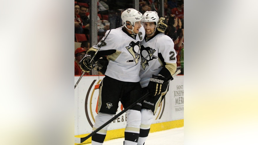 Pittsburgh Penguins' Sidney Crosby (87) celebrates his first-period goal against the Detroit Red Wings with teammate Matt Niskanen (2) during an NHL hockey game on Saturday, Dec. 14, 2013, in Detroit. (AP Photo/Duane Burleson)