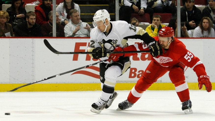 Pittsburgh Penguins' Chuck Kobasew (12) tries to keep Detroit Red Wings' Niklas Kronwall (55), of Sweden, off the puck during the first period of an NHL hockey game on Saturday, Dec. 14, 2013, in Detroit. (AP Photo/Duane Burleson)