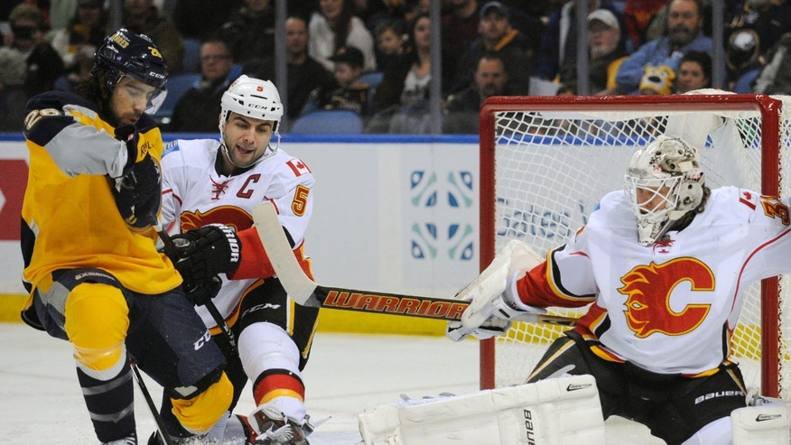 Buffalo Sabres left wing Matt Moulson, left, battles for the puck as Calgary Flames defenseman Mark Giordano (5) and goaltender Karri Ramo (31), of Finland, defend during the first period of an NHL hockey game in Buffalo, N.Y., Saturday Dec. 14, 2013. (AP Photo/Gary Wiepert)