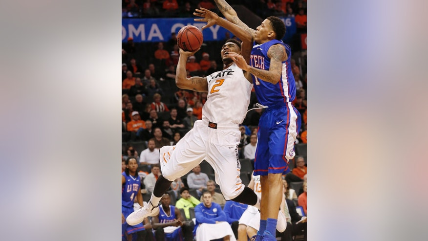 Oklahoma State wing Le'Bryan Nash (2) is fouled by Louisiana Tech forward Michale Kyser (1) as he shoots in the first half of an NCAA college basketball game in Oklahoma City, Saturday, Dec. 14, 2013. (AP Photo/Sue Ogrocki)