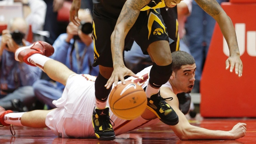Iowa guard Devyn Marble, top, is fouled by Iowa State forward Georges Niang, bottom, while fighting for a loose ball during the first half of an NCAA college basketball game on Friday, Dec. 13, 2013, in Ames, Iowa. (AP Photo/Charlie Neibergall)