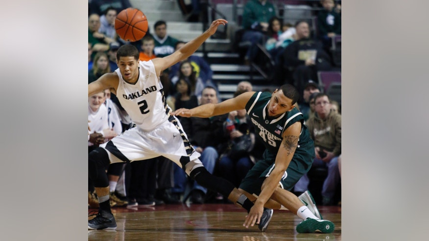 Michigan State's Denzel Valentine, right, and Oakland's Dante Williams (2) collide as they chase a loose ball during the first half of an NCAA college basketball game, Saturday, Dec. 14, 2013, in Auburn Hills, Mich. (AP Photo/Al Goldis)