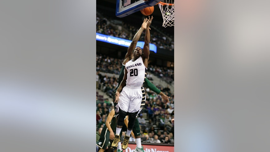 Oakland's Kahlil Felder (20) puts up a layup in front of Michigan State's Branden Dawson during the first half of an NCAA college basketball game, Saturday, Dec. 14, 2013, in Auburn Hills, Mich. (AP Photo/Al Goldis)
