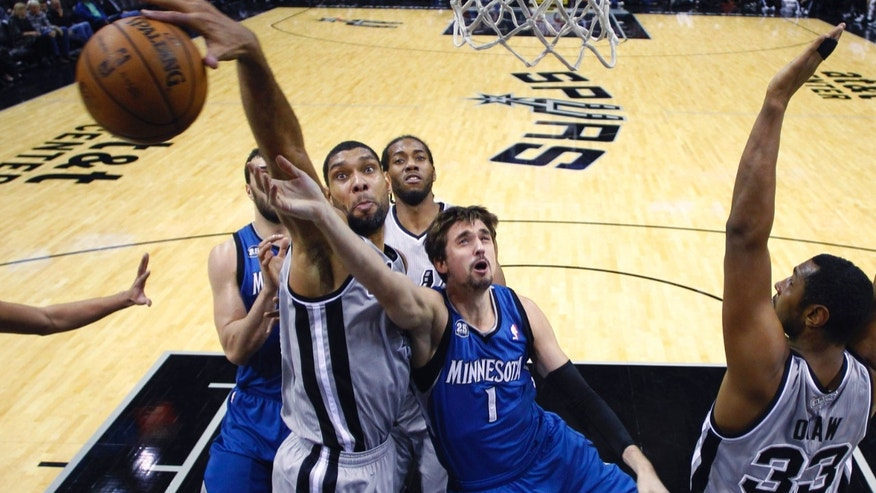 San Antonio Spurs' Tim Duncan, left, blocks Minnesota Timberwolves' Alexey Shved (1) as he tries to score during the first half on an NBA basketball game, Friday, Dec. 13, 2013, in San Antonio.  (AP Photo/Eric Gay)