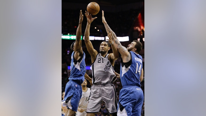 San Antonio Spurs' Tim Duncan (21) drives between Minnesota Timberwolves' Dante Cunningham, left, and Nikola Pekovic (14) during the first half on an NBA basketball game, Friday, Dec. 13, 2013, in San Antonio.  (AP Photo/Eric Gay)