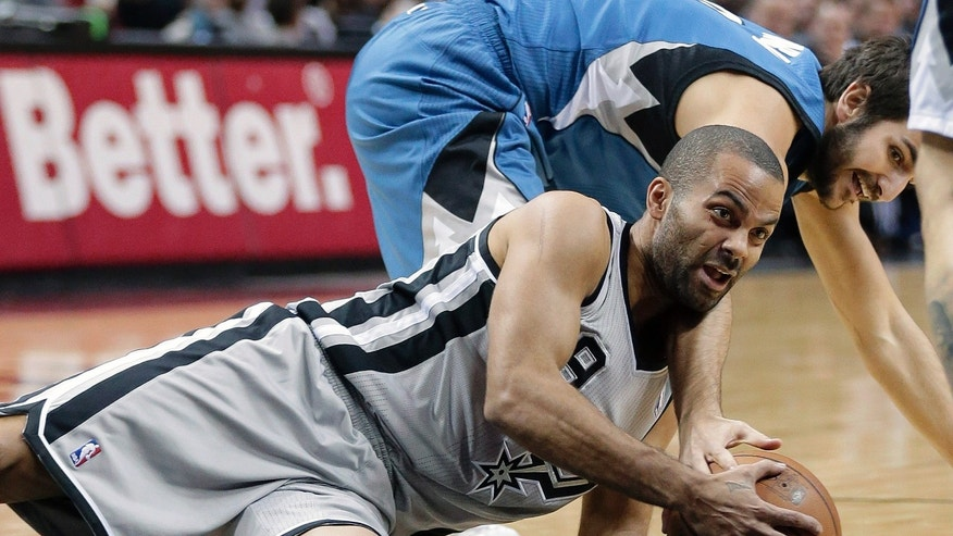 San Antonio Spurs' Tony Parker, front, of France, and Minnesota Timberwolves' Ricky Rubio, back, scramble for a loose ball during the first half on an NBA basketball game, Friday, Dec. 13, 2013, in San Antonio.  (AP Photo/Eric Gay)