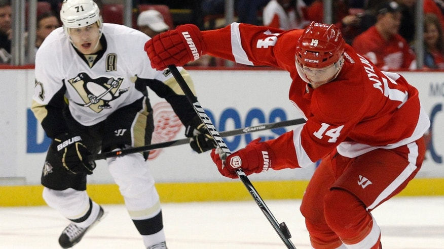 Detroit Red Wings' Gustav Nyquist (14), of Sweden, is pursued by Pittsburgh Penguins' Evgeni Malkin (71), of Russia, as he brings the puck down the ice during the second period of an NHL hockey game on Saturday, Dec. 14, 2013, in Detroit. (AP Photo/Duane Burleson)