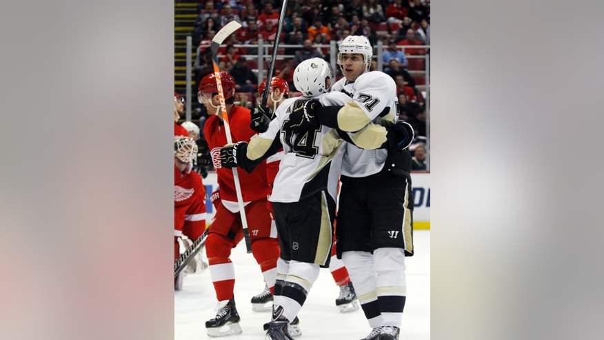 Pittsburgh Penguins' Evgeni Malkin (71), of Russia, celebrates his first-period goal against the Detroit Red Wings with teammate Chris Kunitz (14) during an NHL hockey game on Saturday, Dec. 14, 2013, in Detroit. (AP Photo/Duane Burleson)