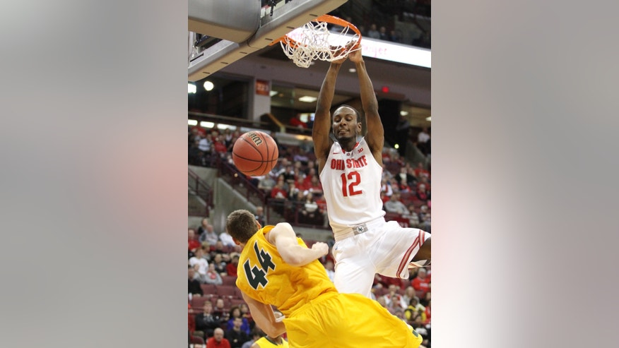 Ohio State's Sam Thompson (12) dunks over North Dakota State's Jordan Aaberg (44) during the first half of an NCAA college basketball game, Saturday, Dec. 14, 2013, in Columbus, Ohio. (AP Photo/Mike Munden)