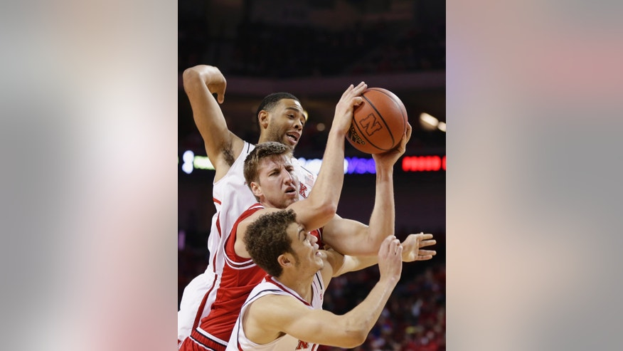 Arkansas State's Kirk Van Slyke, center, wins a rebound against Nebraska's Walter Pitchford, top, and Nebraska's Nathan Hawkins, bottom, in the first half of an NCAA college basketball game in Lincoln, Neb., Saturday, Dec. 14, 2013. (AP Photo/Nati Harnik)
