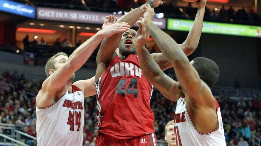 Western Kentucky's George Fant, center, goes up for a shot through the defense of Louisville's Stephan Van Treese, left, and Chane Behanan during the first half of an NCAA college basketball game Saturday, Dec. 14, 2013, in Louisville, Ky. (AP Photo/Timothy D. Easley)