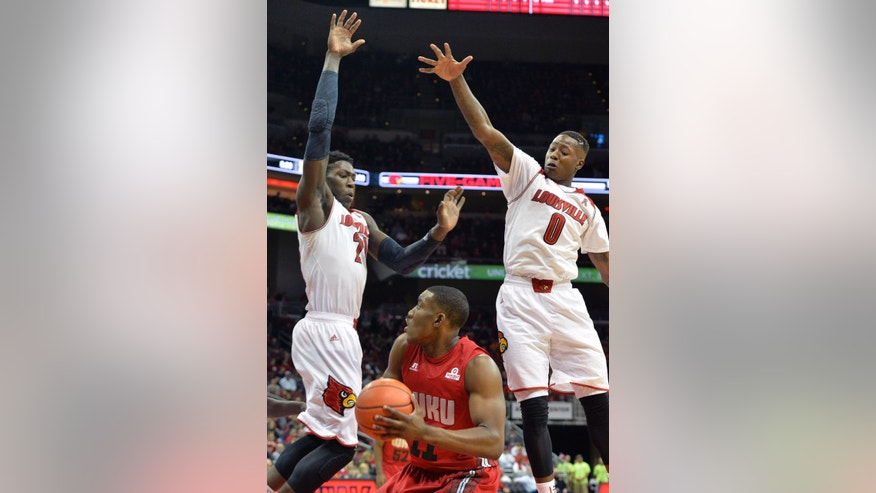 Louisville's Montrezl Harrell, left, and Terry Rozier, right, go up in an attempt to block the shot of Western Kentucky's Aaron Adeoye during the first half of an NCAA college basketball game Saturday, Dec. 14, 2013, in Louisville, Ky. (AP Photo/Timothy D. Easley)