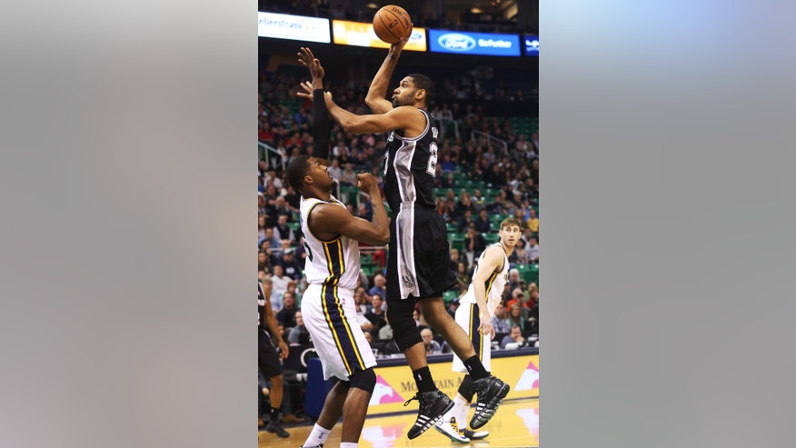 San Antonio Spurs' Tim Duncan, right, shoots the ball as Utah Jazz's Derrick Favors, left, defends in the first half of an NBA basketball game on Saturday, Dec. 14, 2013, in Salt Lake City. (AP Photo/Kim Raff)
