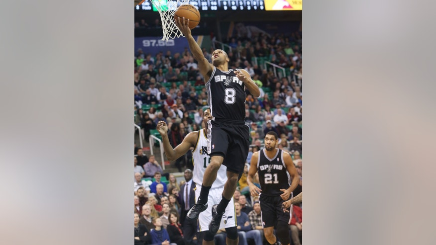San Antonio Spurs' Patty Mills (8) attempts a layup as Utah Jazz's Derrick Favors, back, looks on in the first half of an NBA basketball game on Saturday, Dec. 14, 2013, in Salt Lake City. (AP Photo/Kim Raff)