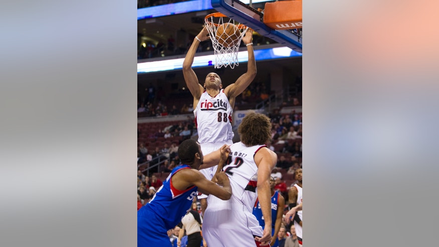 Portland Trail Blazers' Nicolas Batum (88), of France, dunks the ball as Trail Blazers' Robin Lopez, right, blocks out Philadelphia 76ers' Hollis Thompson, left, during the first half of an NBA basketball game on Saturday, Dec. 14, 2013, in Philadelphia. (AP Photo/Chris Szagola)