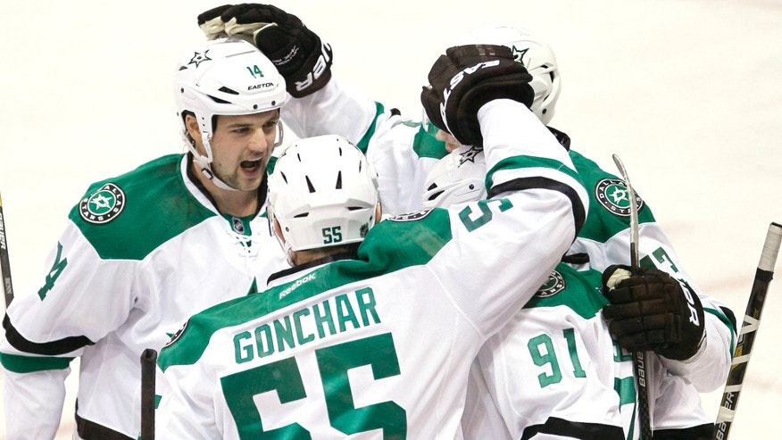 Dallas Stars' Jamie Benn (14), Sergei Gonchar (55), Valeri Nichushkin (43) and Tyler Seguin (91) celebrate Seguin's goal against the Winnipeg Jets during first period of an NHL hockey game in Winnipeg, Manitoba, on Saturday, Dec. 14, 2013. (AP Photo/The Canadian Press, John Woods)