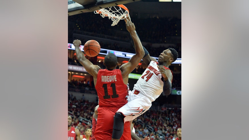 Louisville's Montrezl Harrell, right, dunks over the defense of Western Kentucky's Aaron Adeoye during the second half of an NCAA college basketball game Saturday, Dec. 14, 2013, in Louisville, Ky. Louisville won 79-63. (AP Photo/Timothy D. Easley)