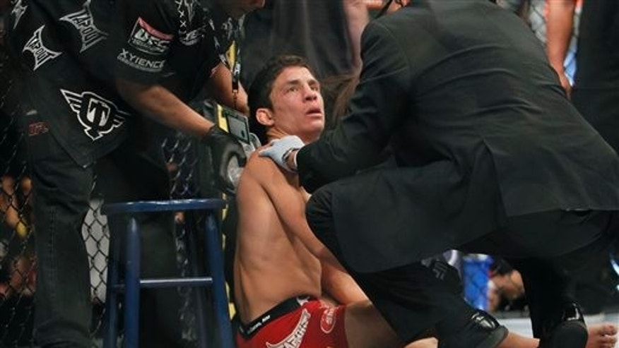 Joseph Benavidez is tended to after being knocked out by Demetrious Johnson in the first round of a UFC flyweight mixed martial arts title fight in Sacramento, Calif., Saturday, Dec. 14, 2013. (AP Photo/Steve Yeater)