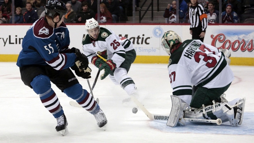 Minnesota Wild goalie Josh Harding (37) stops a shot by Colorado Avalanche left wing Cody McLeod (55) as Wild defenseman Jonas Brodin (25) defends during the first period of an NHL hockey game in Denver on Saturday, Dec. 14, 2013. (AP Photo/Joe Mahoney)