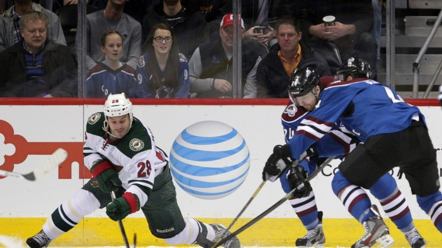 Minnesota Wild center Zenon Konopka (28) reaches for the puck against Colorado Avalanche right wing Marc-Andre Cliche (24) and Avalanche defenseman Tyson Barrie, right, during the first period of an NHL hockey game in Denver on Saturday, Dec. 14, 2013. (AP Photo/Joe Mahoney)