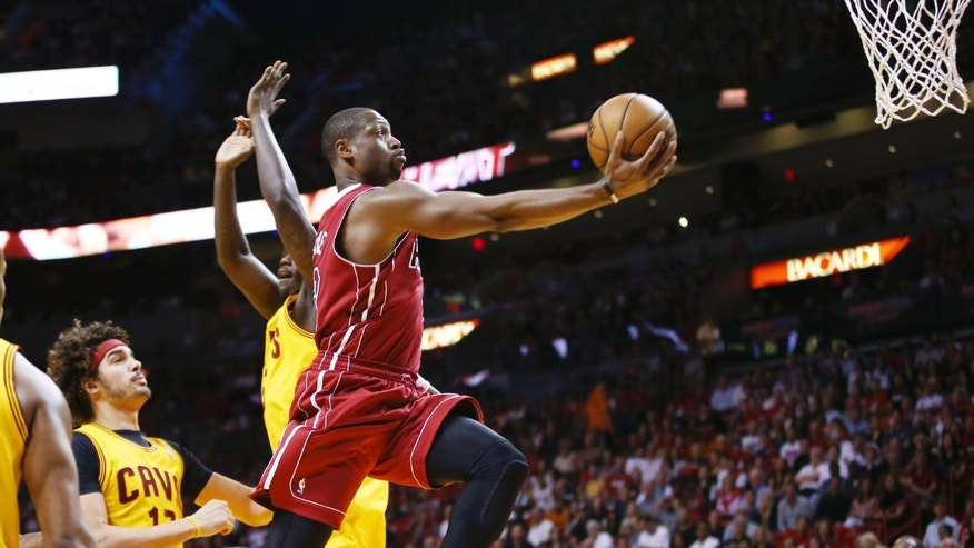 Miami Heat's Dwyane Wade (3) slides past Cleveland Cavaliers' Anthony Bennett (15) and Anderson Varejao (17) for two points during the first half of an NBA basketball game in Miami, Saturday, Dec. 14, 2013. (AP Photo/J Pat Carter)