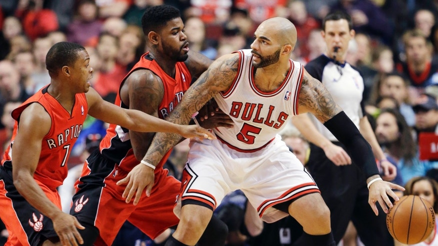 Chicago Bulls forward Carlos Boozer, right, controls the ball as Toronto Raptors forward Amir Johnson, center, and guard Kyle Lowry guard during the first half of an NBA basketball game in Chicago on Saturday, Dec. 14, 2013. (AP Photo/Nam Y. Huh)
