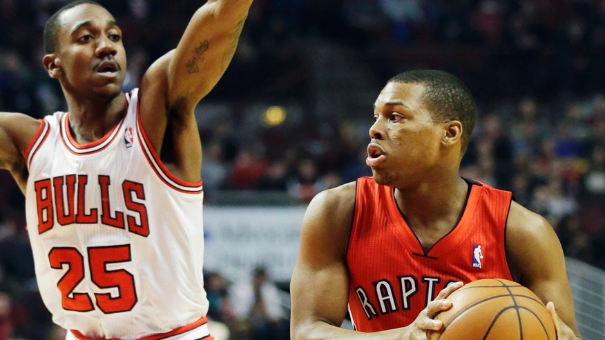 Toronto Raptors guard Kyle Lowry, right, looks to a pass as Chicago Bulls guard Marquis Teague guards during the first half of an NBA basketball game in Chicago on Saturday, Dec. 14, 2013. (AP Photo/Nam Y. Huh)