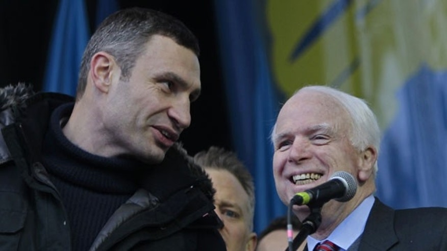 December 15, 2013: Ukrainian lawmaker and chairman of the Ukrainian opposition party Udar (Punch), WBC heavyweight boxing champion Vitali Klitschko, left, speaks to U.S. Senator John McCain during a pro-European Union rally in Independence Square in Kiev, Ukraine. (AP Photo)