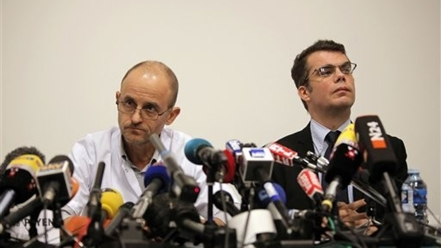 Professor Jean-Francois Payen and assistant director Marc Penaud during a press conference at the Grenoble hospital, in the French Alps, Monday, Dec. 30, 2013.