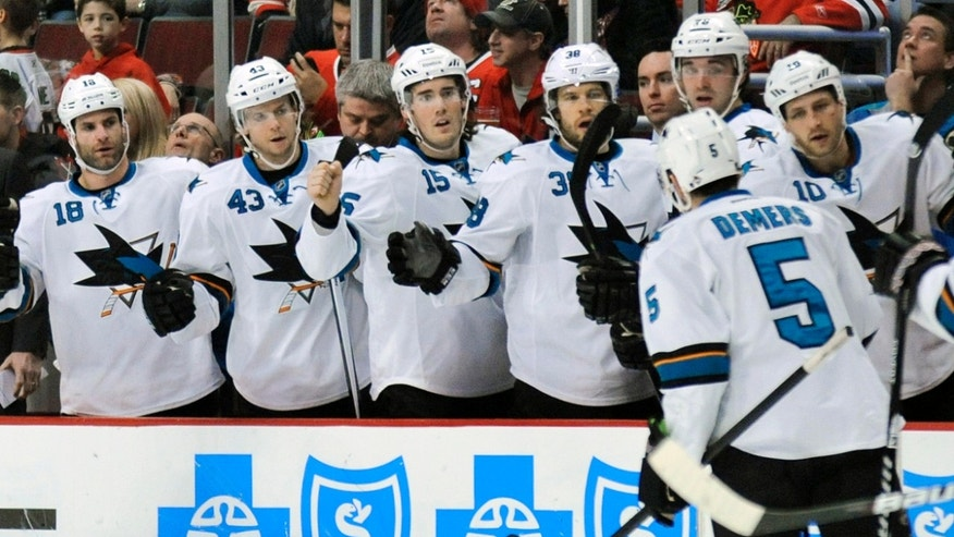 San Jose Sharks' Jason Demers (5) celebrates with teammates after scoring a goal during the first period of an NHL hockey game against the Chicago Blackhawks in Chicago, Sunday, Jan. 5, 2013. (AP Photo/Paul Beaty)