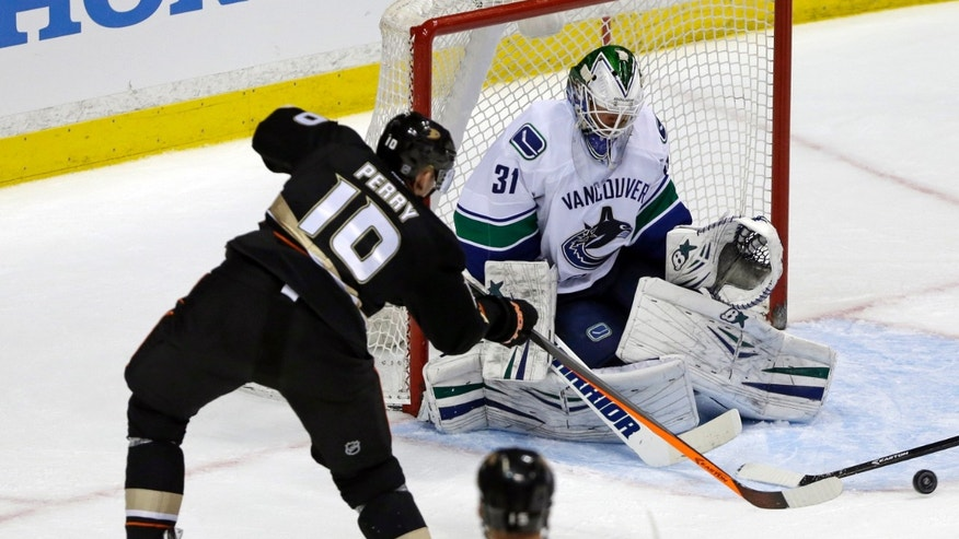 Vancouver Canucks goalie Eddie Lack (31) defends as Anaheim Ducks right winger Corey Perry (10) attacks in the second period of an NHL hockey game in Anaheim, Calif., Sunday, Jan. 5, 2014. (AP Photo/Reed Saxon)