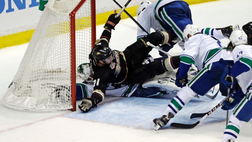 Vancouver Canucks goalie Eddie Lack (31) winds up at the bottom of a pileup in goal with Anaheim Ducks right winger Kyle Palmieri (21) in the second period of an NHL hockey game in Anaheim, Calif., Sunday, Jan. 5, 2014. (AP Photo/Reed Saxon)