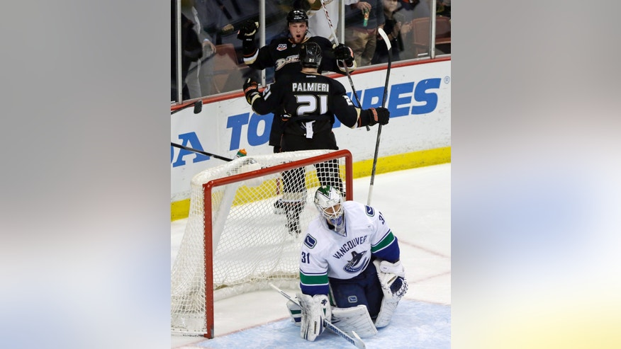 Anaheim Ducks left winger Matt Beleskey (39), rear, and right winger Kyle Palmieri (51) celebrate Beleskey's goal over Vancouver Canucks goalie Eddie Lack (31) in the second period of an NHL hockey game in Anaheim, Calif., Sunday, Jan. 5, 2014. (AP Photo/Reed Saxon)
