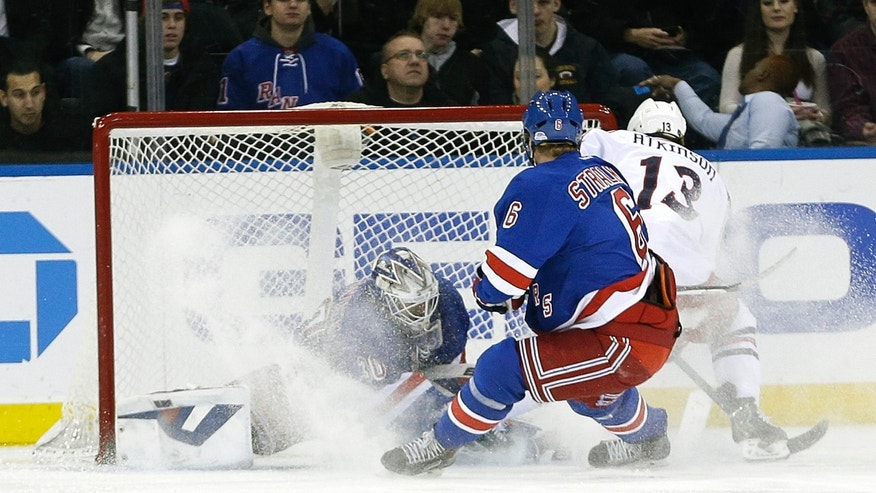 Columbus Blue Jackets' Cam Atkinson (13) scores on New York Rangers goalie Henrik Lundqvist (30), of Sweden, during the second period of an NHL hockey game, Monday, Jan. 6, 2014, in New York.  (AP Photo/Frank Franklin II)