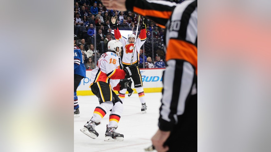 Calgary Flames center Joe Colborne (8) celebrates his goal against the Colorado Avalanche in the second period of an NHL game in Denver on Monday, Jan. 6, 2014. Calgary Flames right wing Kevin Westgarth (15) skates toward Colborne. (AP Photo/Joe Mahoney)