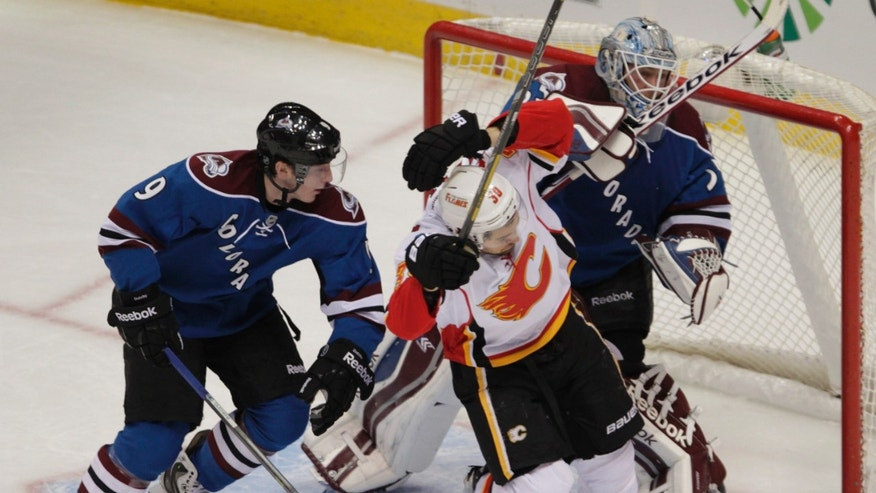 Colorado Avalanche goalie Jean-Sebastien Giguere (35) pushes Calgary Flames left wing T.J. Galiardi (39) as Avalanche center Matt Duchene (9) defends in the first period of an NHL game in Denver on Monday, Jan. 6, 2014. (AP Photo/Joe Mahoney)