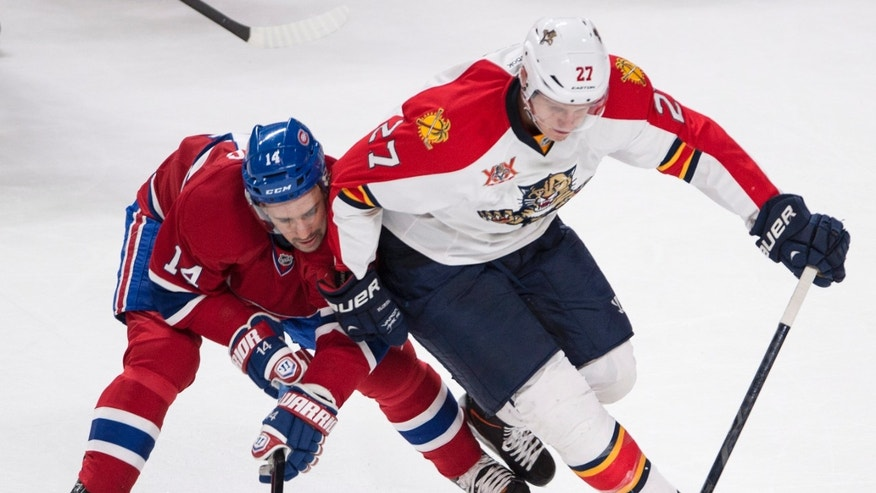 Montreal Canadiens' Tomas Plekanec, left, gets an elbow from Florida Panthers Nick Bjugstad during first period of an NHL hockey game, Monday, Jan. 6, 2014 in Montreal. (AP Photo/The Canadian Press, Paul Chiasson)