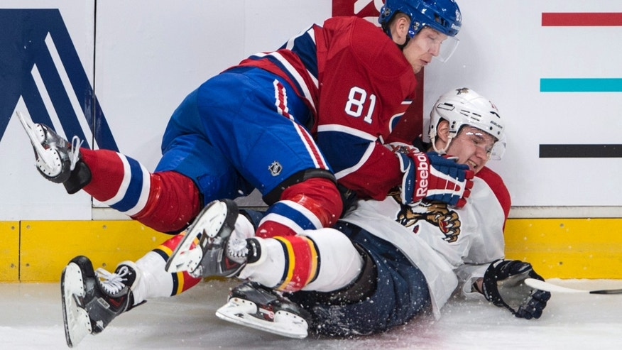 Montreal Canadiens' Lars Eller (81) falls over Florida Panthers' Aleksander Barkov during first period of an NHL hockey game, Monday, Jan. 6, 2014 in Montreal. (AP Photo/The Canadian Press, Paul Chiasson)