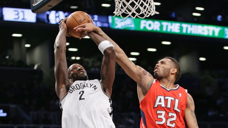 Atlanta Hawks forward Mike Scott (32) fouls Brooklyn Nets forward Kevin Garnett (2) in the first half of their NBA basketball game at the Barclays Center, Monday, Jan. 6, 2014, in New York. (AP Photo/Kathy Willens)