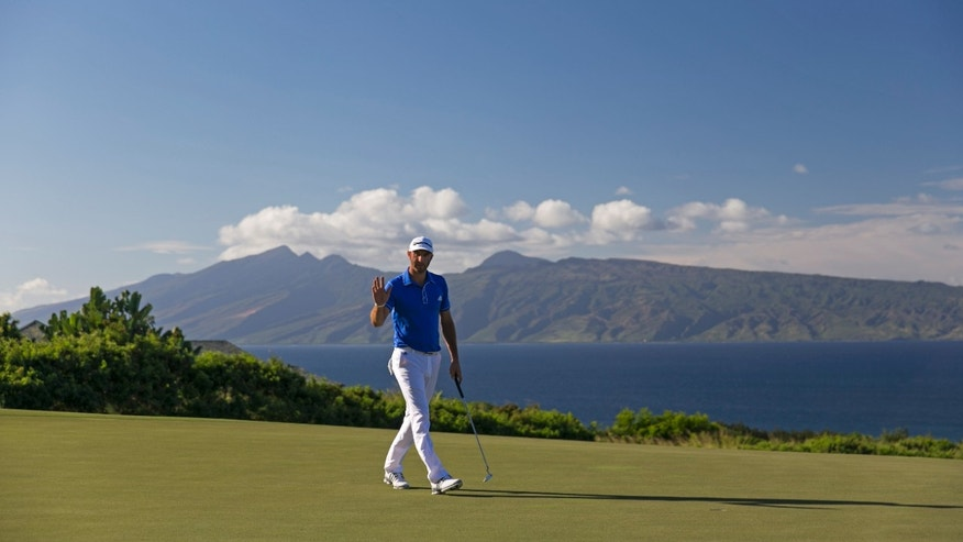 Dustin Johnson waves to the gallery on the 14th green during the third round of the Tournament of Champions golf tournament, Sunday, Jan. 5, 2014, in Kapalua, Hawaii. (AP Photo/Marco Garcia)