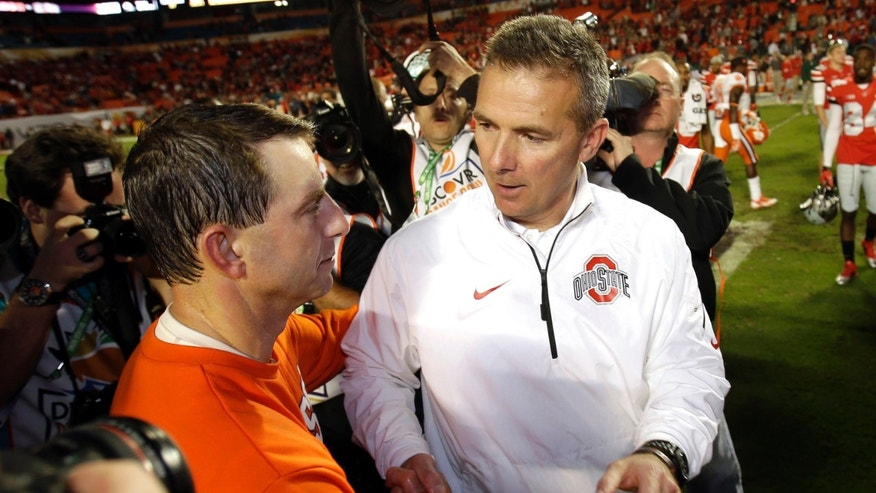 FILE - In this Jan. 4, 2014 photo, Ohio State head coach Urban Meyer, right, shakes hands with Clemson head coach Dabo Swinney after the Orange Bowl NCAA college football game in Miami Gardens, Fla. Clemson defeated Ohio State 40-35. The Buckeyes ended the season with a two game losing streak. (AP Photo/Wilfredo Lee, File)