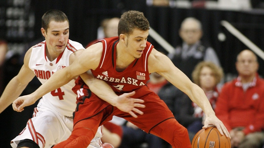Ohio State's Aaron Craft (4) reaches for the ball against Nebraska's Nathan Hawkins (4) during the first half of an NCAA college basketball game Saturday, Jan. 4, 2014, in Columbus, Ohio. (AP Photo/Mike Munden)