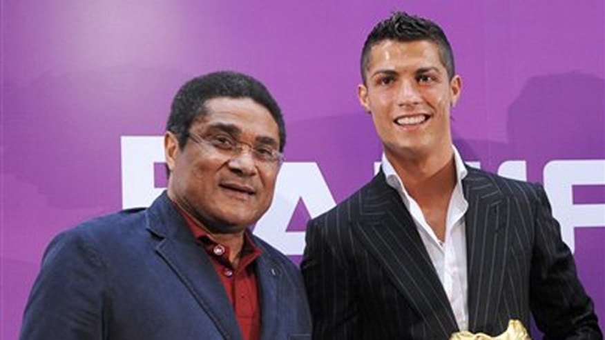 FILE - In this Sept. 13, 2008 file photo, Portuguese soccer player Cristiano Ronaldo holds his European Golden Boot while posing for a photo with Eusebio, in Funchal, in the Portuguese island of Madeira. Eusebio won the trophy in 1968 and 1973. Eusebio, the Portuguese football star who was born into poverty in Africa but became an international sporting icon and was voted one of the 10 best players of all time, has died of heart failure aged 71, Sunday, Jan. 5 2014. (AP Photo/Helder Santos, File)