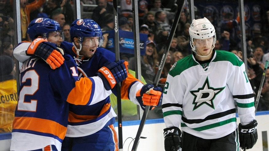 New York Islanders' Josh Bailey (12) hugs Peter Regin (16) as Dallas Stars' Alex Chiasson (12) reacts after Regin scored in the second period of an NHL hockey game on Monday, Jan. 6, 2014, in Uniondale, N.Y. (AP Photo/Kathy Kmonicek)