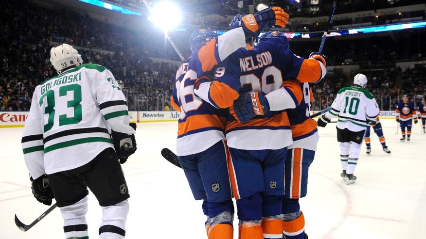 New York Islanders' Thomas Vanek (26), Brock Nelson (29) and John Tavares (91) celebrate Nelson's goal as Dallas Stars' Alex Goligoski (33) skates away in the third period of an NHL hockey game on Monday, Jan. 6, 2014, in Uniondale, N.Y. (AP Photo/Kathy Kmonicek)