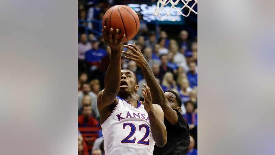 Kansas' Andrew Wiggins (22) puts up a shot under pressure from San Diego State's Dwayne Polee II during the first half of an NCAA college basketball game Sunday, Jan. 5, 2014, in Lawrence, Kan. (AP Photo/Charlie Riedel)