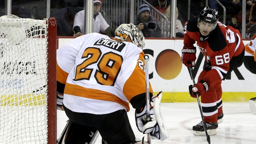 Philadelphia Flyers goalie Ray Emery (29) deflects a shot as New Jersey Devils right wing Jaromir Jagr (68), of the Czech Republic, watches during the second period of an NHL hockey game, Tuesday, Jan. 7, 2014, in Newark, N.J. (AP Photo/Julio Cortez)
